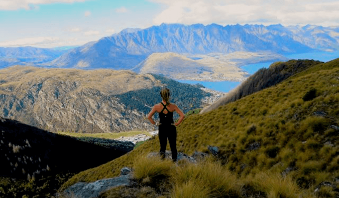 woman dressed in sportsware standing high in the mountains looking down at the view hands on hips