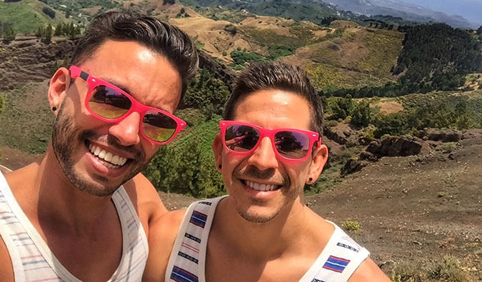 Image of Auston and David smiling wearing matching red sunglasses with a scening background