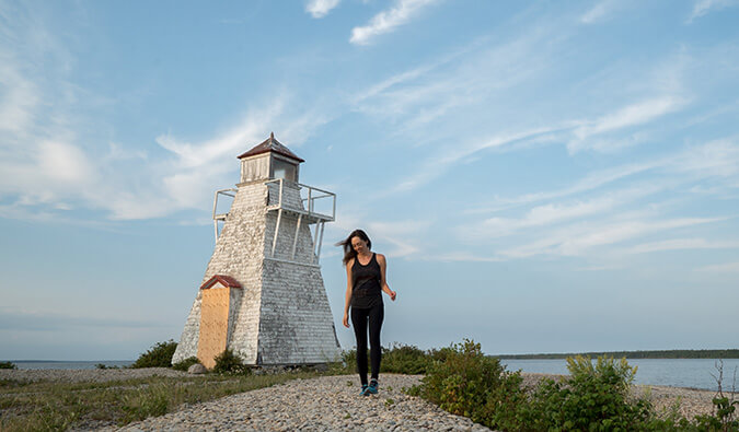 Kirstin walking towards the camera with a lighthouse in the background