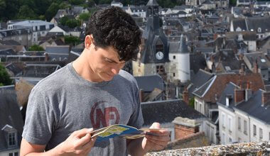 Nomadic Matt looking at a map in a city
