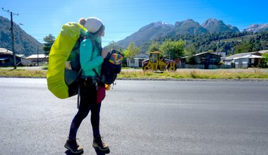 female backpacker walking down a quiet street with mountains in the distance