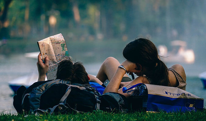 a male and female backpacker relaxing on the grass leaning on their backpacks reading a map