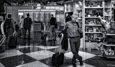 A black and white photo of a solo traveler at the airport looking at his phone