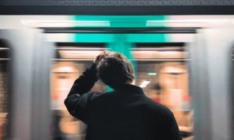 man scratching his head standing on a platform with a train passing by