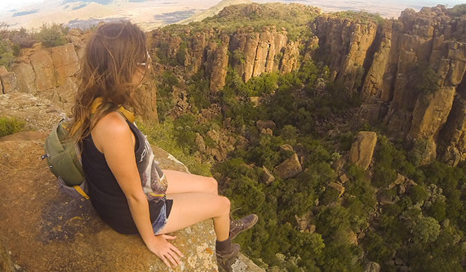 Kirstin Farm sat on a rock in South Africa with her legs dangling over the edge