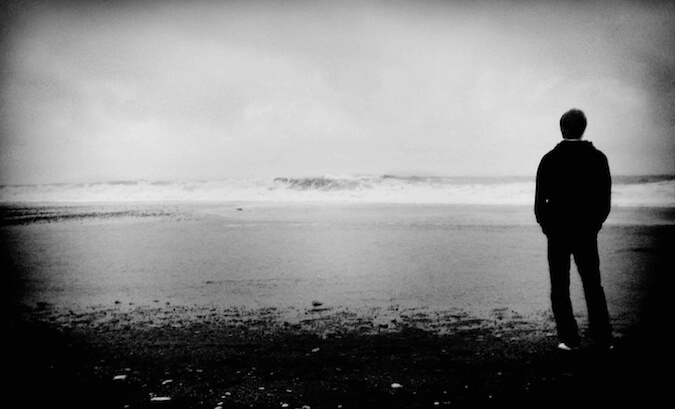Black and white photo of a guy overlooking a lake