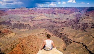 man sat on a rock front and centre in background surrounded by canyon