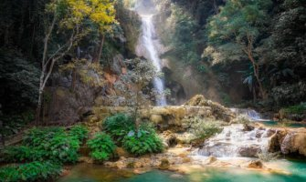 A picturesque waterfall surrounded by jungle in Laos