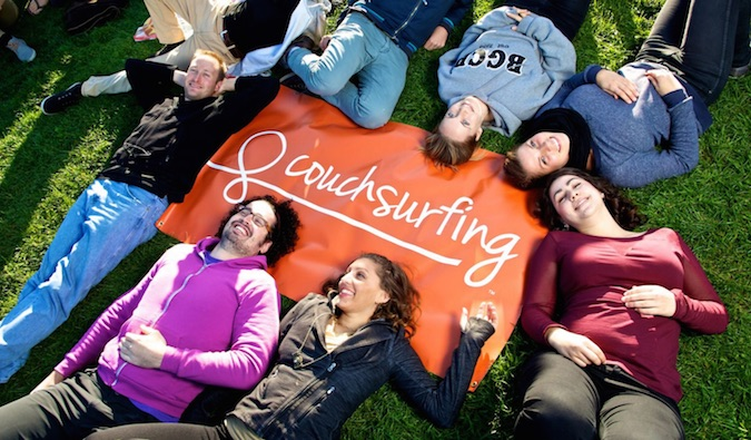 People in front of a Couchsurfing sign