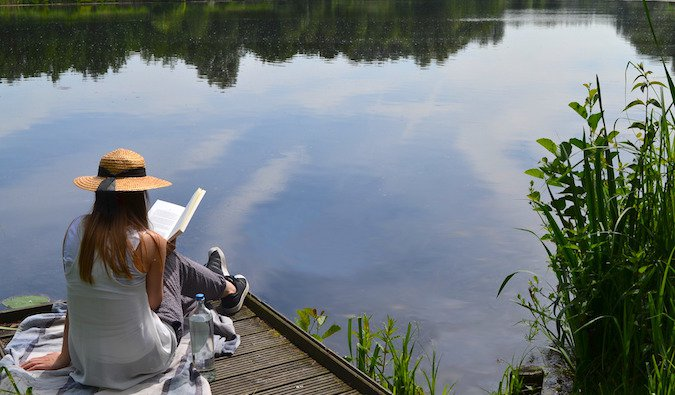A woman reading a book on a lake