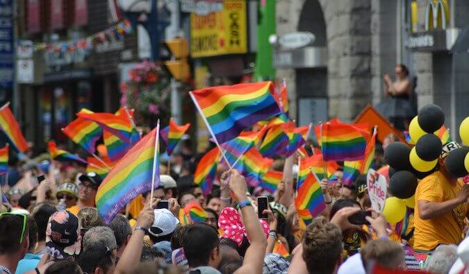 A crowd of people on a street at a pride event waving rainbow flags