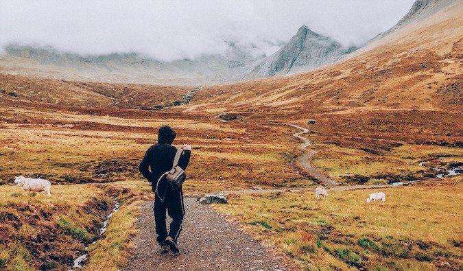 A guy wandering near mountains on a foggy day