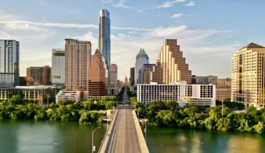 he towering skyline of Austin, Texas as seen from over a bridge