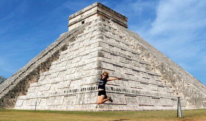 Woman jumping in front of Chichen Itza Mayan ruins in Mexico