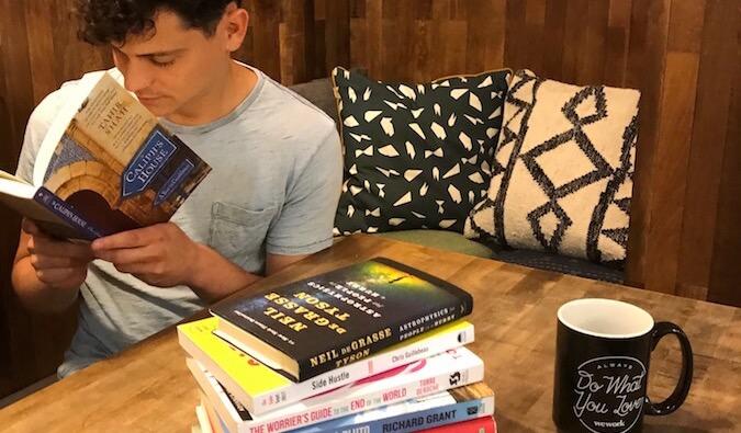 Nomadic Matt reading books in wework