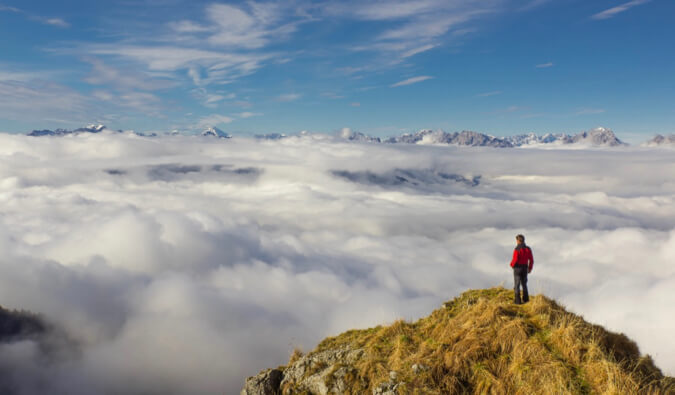 A man standing on the top of the mountains overlooking clouds