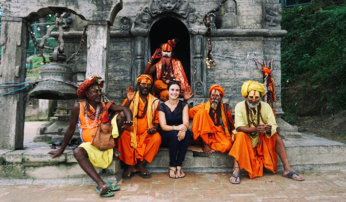 Woman sat outside a temple in India with 5 men dressed in traditional clothing and their faces painted