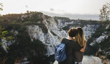 two women hugging looking out over the view of the mountains