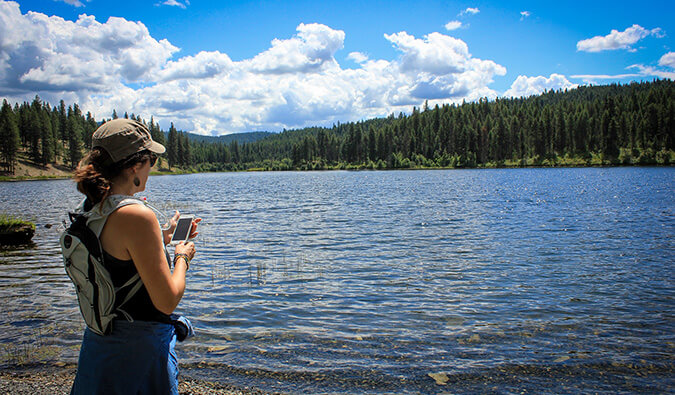 woman on her smart phone standing next to a large scenic lake