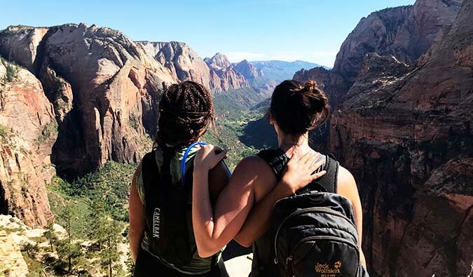 Two girls with their arms around each other wearing backpacks looking out to a view of mountains