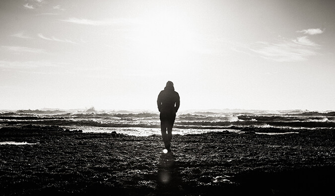 man walking alone on a beach. Image is black and white