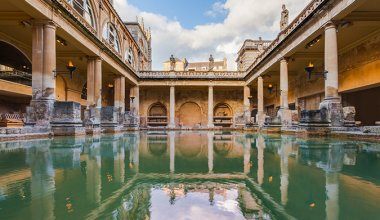 Roman baths in Bristol water with statues and pillars surrounding