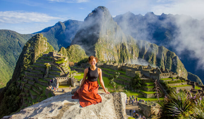 woman sat on a rock in foreground with Machu Picchu in he background