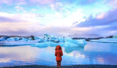 solo female traveler in a read coat at the Glacier Lagoon in Iceland