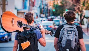 two backpackers walking down a street one is holding a guitar over his shoulder