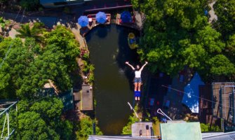 Woman bungee jumping over water surrounded by trees arms out facing up to camera