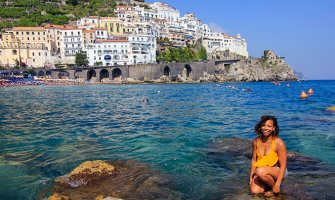 smiling woman in yellow top crouching on a rock in the sea with houses in the background build into the cliff side