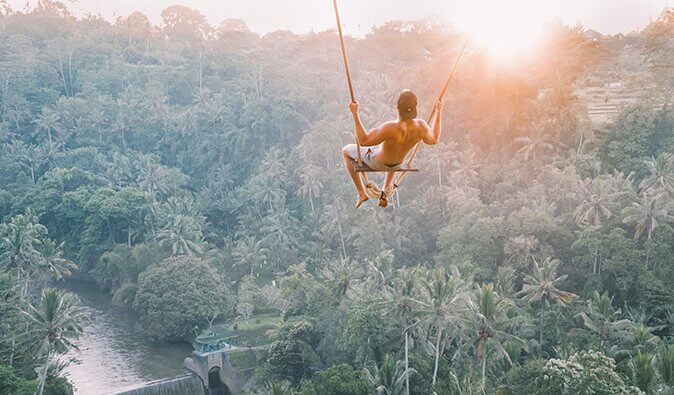 A man swinging on a high swing in the jungle