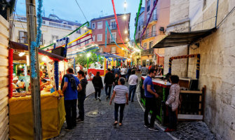people walking down a market street in lisbon, portugal