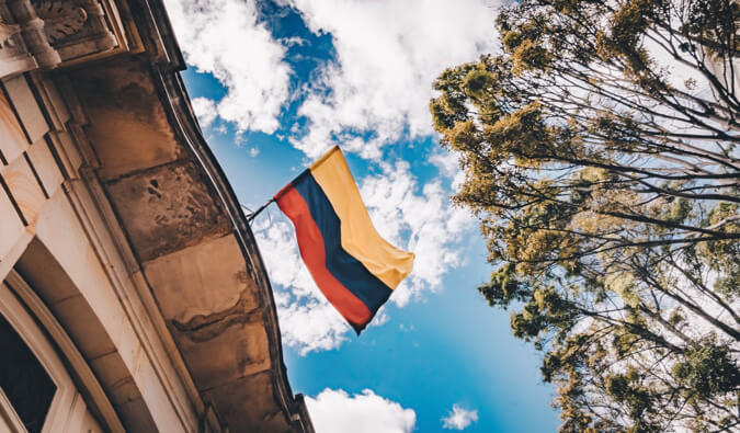 A colorful Colombian flag hanging from an old building.