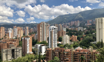 A photo of Medellin's buildings under a bright blue sky
