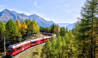 A red train going through the Swiss mountains
