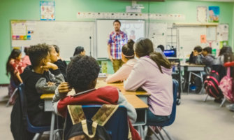 A man teaching English to a classroom of students abroad