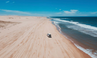 A wide open beach in Australia with a 4x4 vehicle driving in the sand