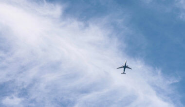 A lone airplane flying through a bright blue sky