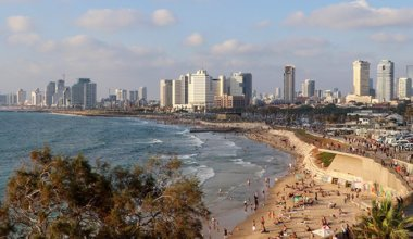 the beach in Tel Aviv with skyscrapers in the background