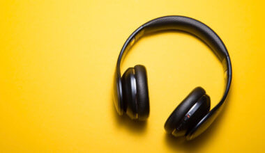 A pair of black headphones on a bright orange background