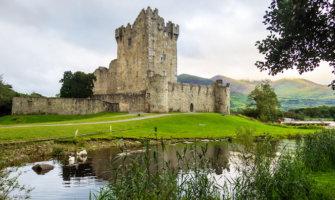 an Irish castle tower on a still lake set against green hills