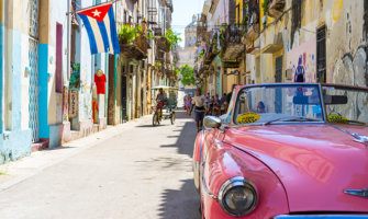 a classic pink car on the colorful streets of Havana, with a Cuban flag in the background