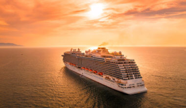 A huge cruise ship sailing into the sunset on calm waters
