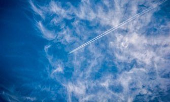 A commercial airplane high in the sky, cutting the the clouds and a blue sky
