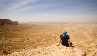 A solo traveler sitting on a cliff in the desert in Saudi Arabia