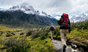A hiker walking on a trail toward snow-capped mountains