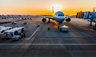 A solitary airplane at an airport during sunset