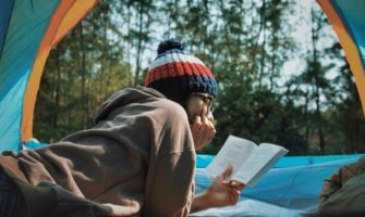 A traveler reading a book while inside a tent