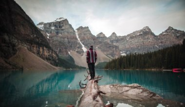 A solo traveler standing on a log in Alberta, Canada